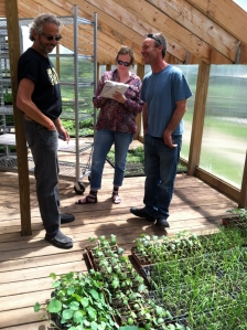 Zingerman's co-founder Ari Weinzweig and Cornman Farms farmer Alex talk with a reporter in the greenhouse